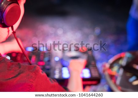 Music Concepts. DJ is rhythm music with Controller and mixer. DJ is playing the song at the party. Young are adjusting the music with the controller. The fun of music and light colors. #1041644260