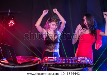 Music Concepts. DJ is rhythm music with Controller and mixer. DJ is playing the song at the party. Young are adjusting the music with the controller. The fun of music and light colors. #1041644443