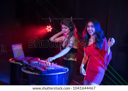 Music Concepts. DJ is rhythm music with Controller and mixer. DJ is playing the song at the party. Young are adjusting the music with the controller. The fun of music and light colors. #1041644467