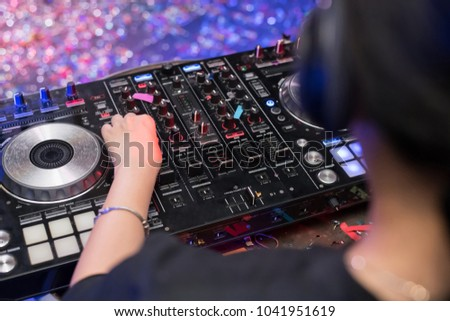 Music Concepts. DJ is rhythm music with Controller and mixer. DJ is playing the song at the party. Young are adjusting the music with the controller. The fun of music and light colors. #1041951619