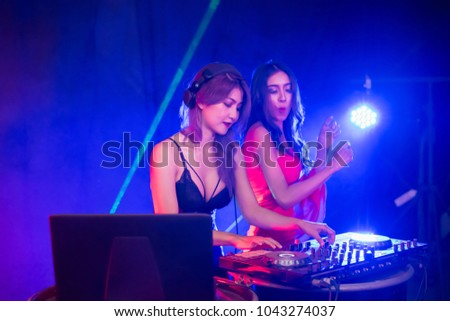 Music Concepts. DJ is rhythm music with Controller and mixer. DJ is playing the song at the party. Young are adjusting the music with the controller. The fun of music and light colors. #1043274037