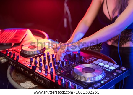 Music Concepts. DJ is rhythm music with Controller and mixer. DJ is playing the song at the party. Young are adjusting the music with the controller. The fun of music and light colors. #1081382261