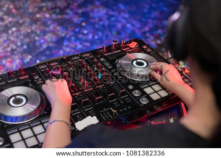 Music Concepts. DJ is rhythm music with Controller and mixer. DJ is playing the song at the party. Young are adjusting the music with the controller. The fun of music and light colors. #1081382336