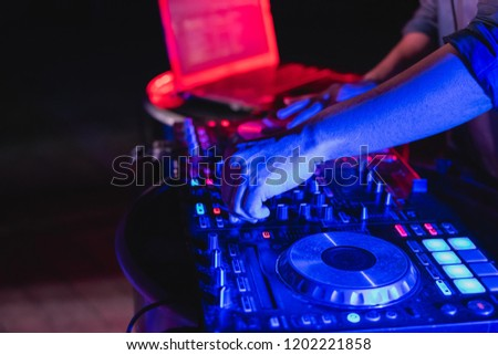 Music Concepts. DJ is rhythm music with Controller and mixer. DJ is playing the song at the party. Young are adjusting the music with the controller. The fun of music and light colors. #1202221858