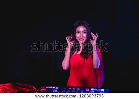 Music Concepts. DJ is rhythm music with Controller and mixer. DJ is playing the song at the party. Young are adjusting the music with the controller. The fun of music and light colors. #1203093793