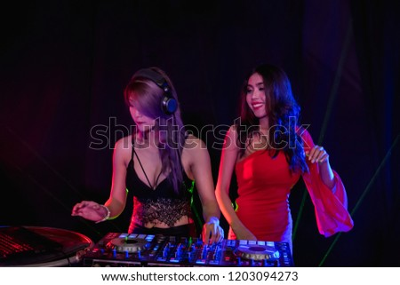 Music Concepts. DJ is rhythm music with Controller and mixer. DJ is playing the song at the party. Young are adjusting the music with the controller. The fun of music and light colors. #1203094273