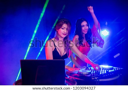 Music Concepts. DJ is rhythm music with Controller and mixer. DJ is playing the song at the party. Young are adjusting the music with the controller. The fun of music and light colors. #1203094327