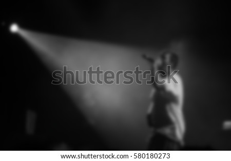 Music concert of rap singer in night club.Famous rapper sing in mic on stage.Bright concert lighting scene.Entertainment event,performing arts.Blurred background.Artist with microphone on club stage