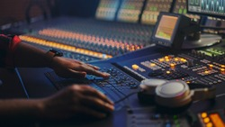 Music Creator, Musician, Artist Works in the Music Record Studio, Uses Surface Control Desk Equalizer Mixer. Buttons, Faders, Sliders to Broadcast, Record, Play Hit Song. Close-up Focus on Hands