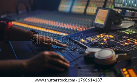Music Creator, Musician, Artist Works in the Music Record Studio, Uses Surface Control Desk Equalizer Mixer. Buttons, Faders, Sliders to Broadcast, Record, Play Hit Song. Close-up Focus on Hands Foto stock ©