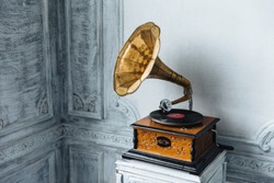 Music device. Old gramophone with plate or vinyl disk on wooden box. Antique brass record player. Gramophone with horn speaker. Retro entertainment concept.