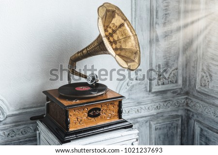Music device. Old gramophone with plate or vinyl disk on wooden box. Antique brass record player. Gramophone with horn speaker. Retro entertainment concept. #1021237693