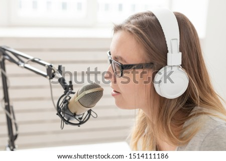 Music, dj, blogging and broadcasting concept - Female radio host with a funny expression, close-up