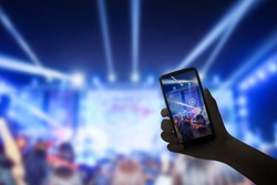 Music fans takes smartphone video records at concert.