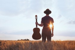 music festival background, silhouette of musician artist with acoustic guitar at sunset field