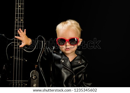 Music for everyone. Adorable small music fan. Small musician. Little rock star. Child boy with guitar. Little guitarist in rocker jacket. Rock style child. Rock and roll music performer. #1235345602