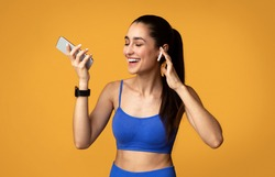 Music For Workout. Portrait Of Smiling Young Slim Lady Wearing Wireless Earphones, Enjoying Favorite Song And Playlist For Training, Holding Smartphone Isolated Over Orange Studio Background