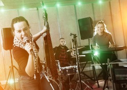 Music garage band with passionate emotional woman vocalist and guitarist practicing on rehearsal base