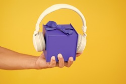 music gift conept. gift box with headphones. male hand hold present yellow backdrop. modern headset. what is inside. audio accessories sale. christmas music gift. musical present. convenient delivery.