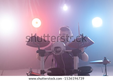 Music, interests, hobby and people concept - young man playing the electronic drums