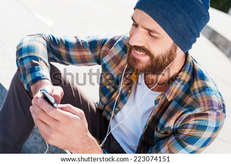 Music is my life Handsome young bearded man smiling while listening to music