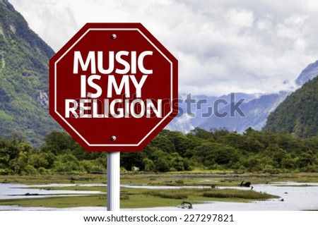 Music Is My Religion written on red road sign with landscape background