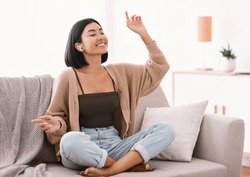 Music Lover Concept. Portrait of smiling asian woman wearing wireless earbuds listening to favorite song, sitting on sofa in living room. Happy millennial lady resting on couch and dancing