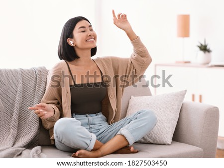 Music Lover Concept. Portrait of smiling asian woman wearing wireless earbuds listening to favorite song, sitting on sofa in living room. Happy millennial lady resting on couch and dancing Stock photo ©