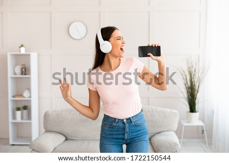 Music Lover. Girl In Earphones Using Phone Listening Song And Singing Standing At Home.