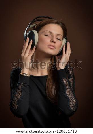 Music lover. Portrait of woman in headphones enjoying the music, dark brown background