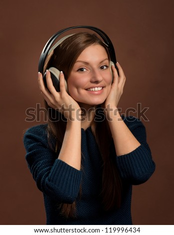 Music lover. Portrait of young smiling woman in headphones, dark brown background