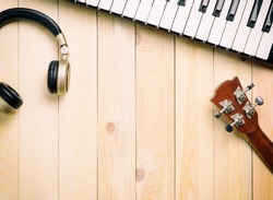 Music making instrument including guitar headphone music synthesizer keyboard on wooden surface for Music and sound banner poster concept for advertisement used.