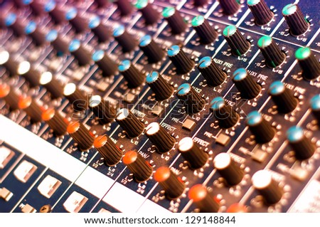 Music mixer with close-up of controls in nightclub with colorful lights
