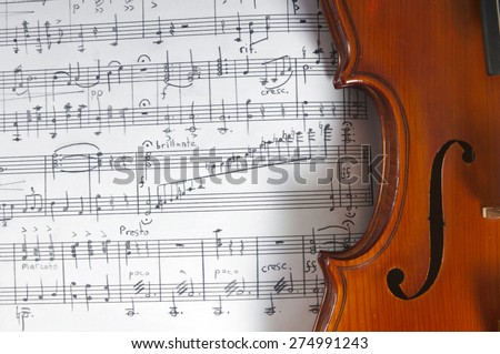 Music notes and violin on table