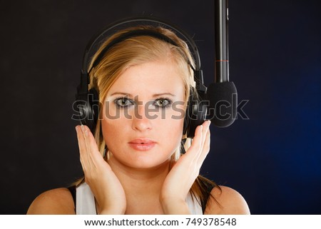 Music, passion, stage-fright concept. Blonde young woman singing to microphone and wearing big headphones on her head performing songs in studio. #749378548