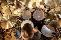 music, people, musical instruments and entertainment concept - male musician or drummer playing drum kit at studio over holidays lights background