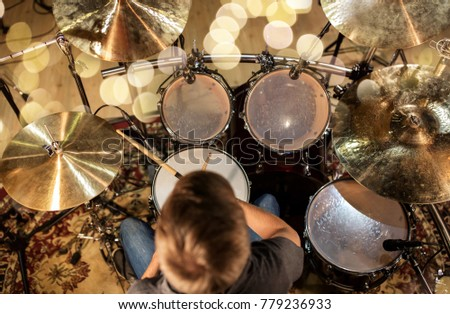 music, people, musical instruments and entertainment concept - male musician or drummer playing drum kit at studio over holidays lights background #779236933