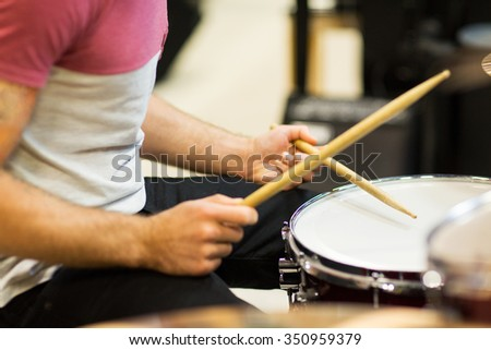 music, people, musical instruments and entertainment concept - male musician playing cymbals and pointing drumstick to you at music store #350959379