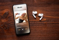 Music player on screen of mobile phone and wireless earbuds on wooden surface