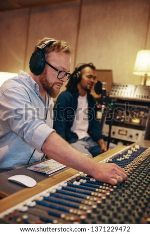 Music producer adjusting levels while listening to a young African American recording artist singing into a microphone in a recording studio #1371229472