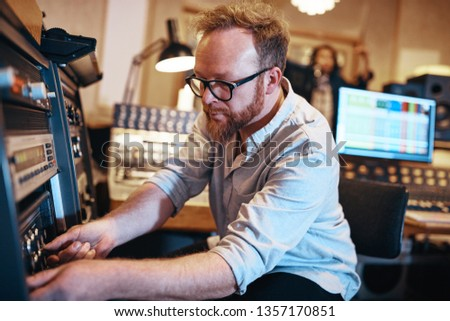 Music producer adjusting sound levels during a session with a young singer in his recording studio #1357170851