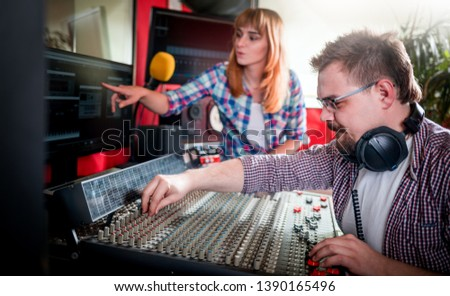 Music producer and musician in recording studio using soundboard for mixing sound #1390165496