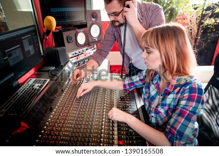 Music producer and musician in recording studio using soundboard for mixing sound #1390165508