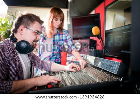 Music producer and musician in recording studio using soundboard for mixing sound #1391934626