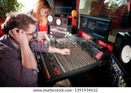 Music producer and musician in recording studio using soundboard for mixing sound #1391934632