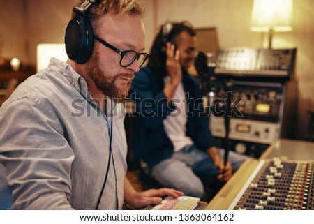 Music producer listening to a young African American recording artist singing into a microphone in a recording studio #1363064162