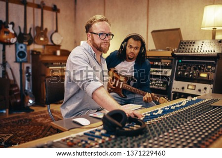 Music producer making adjustments on a soundboard with a young African American musician playing guitar in the background #1371229460