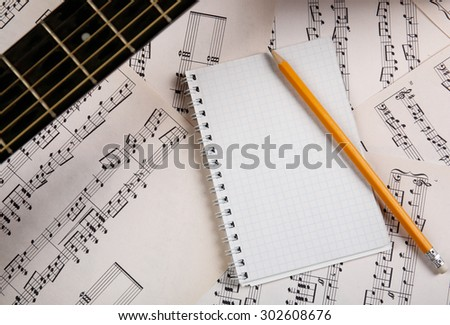 Music recording scene with guitar and memo pad on music sheets background