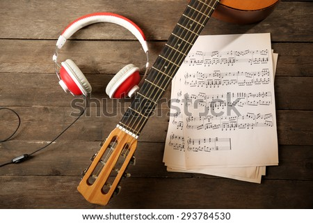 Music recording scene with guitar, music sheets and headphones on wooden table, closeup