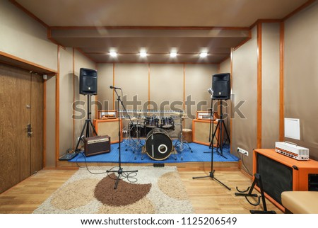 Music rehearsal space with drum kit and musical equipment. Сток-фото ©